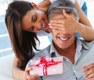 Happy woman covering her husband's eyes to surprise him with a gift